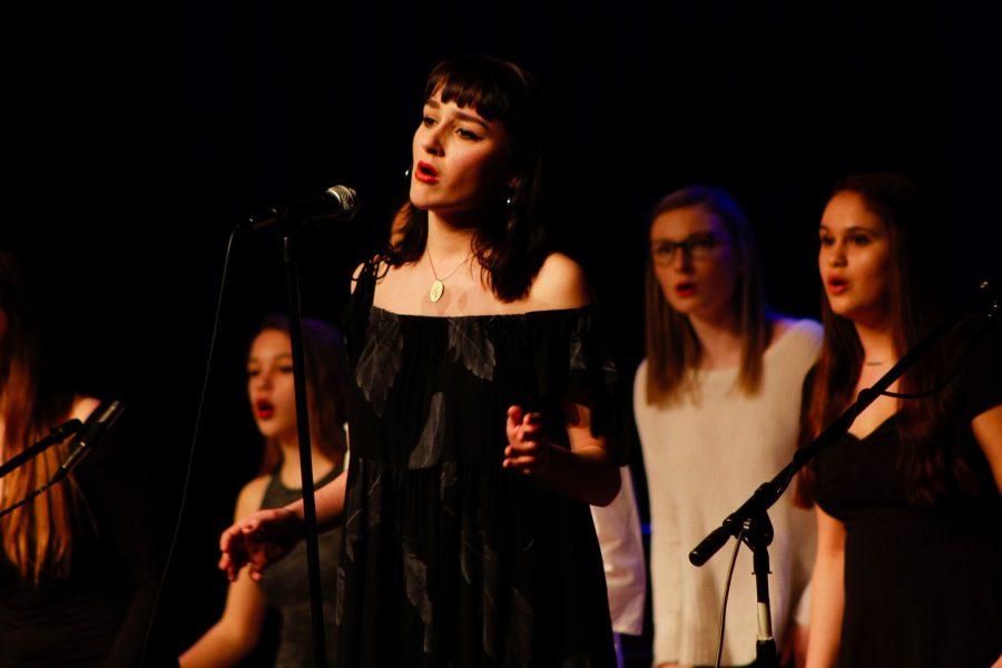 Senior+Chloe+Bernier+leads+her+a+cappella+group%2C+Ladies+First%2C+in+their+rendition+of+%22Black+Horse+and+a+Cherry+Tree%22+by+KT+Tundtall+at+Acapocalypse+on+March+13.+