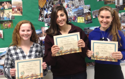 Emily Lowe, Olivia Giorlandino, and Thea Hickey pose with certificates in honor of their travel scholarships.