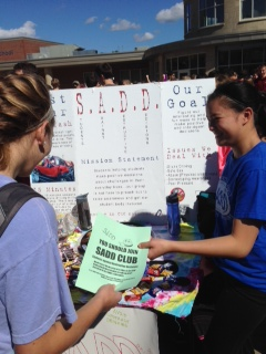 Sophomore Jordan Young passes out a flyer for the SADD club to fellow sophomore, Jackie Lambert.