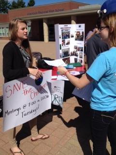 Senior Megan Walsh hands Annie Balunas, senior, a flyer to help save the children
