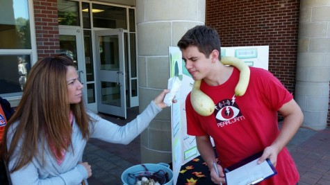 Junior Alex VanAntwerp shows off his fig necklace and tomato for the environmental club.