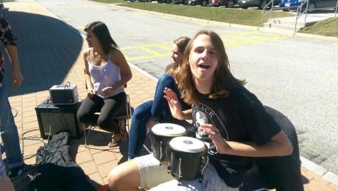 Junior Michael Dutko slams on the bongos beside the Algonquin acoustic club.