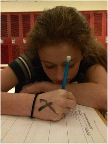 Freshman Tabby Slingluff works on homework in the girls locker room after school.