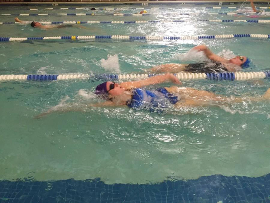 Members of the girls and boys swim teams swim laps at practice on Friday, December 11.
