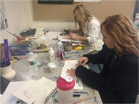 Focused on their elaborate paintings, seniors Kate Massucco and Mackenzie Hostage sit in their everyday corner while watching an episode of Grey's Anatomy on their cell phone in George Hancin's AP Art Class.