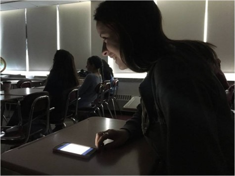 While opening an app on her phone, junior Lizzy Quill laughs at a classmate's joke about her not paying attention.