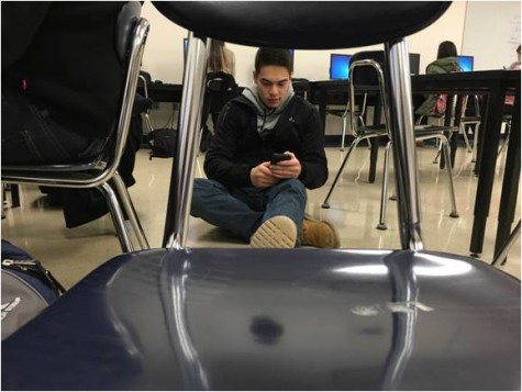 "Senior Nick Hong relaxes on the floor and takes a break after he said, ""I'm tired of sitting in chairs."""