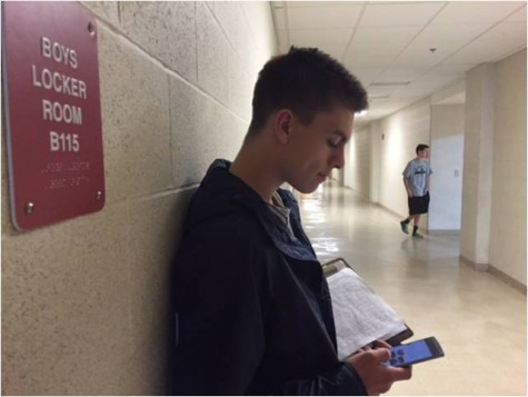 Checking his phone, senior Andrew Travins waits to check in new people before the start of practice.