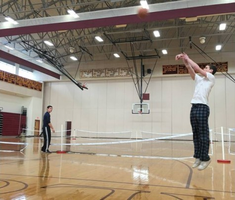 Before seventh period gym class, senior Gavin Boyden takes a jump shot as senior classmate Nolan Kessinger watches from a distance.
