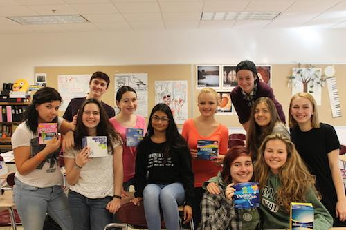 The She-Hawks gather around various feminine hygiene products that were donated over the three-week collection period that was aimed at helping homeless women get the tampons and pads they need. Club members delivered the donated products to the Worcester YWCA.