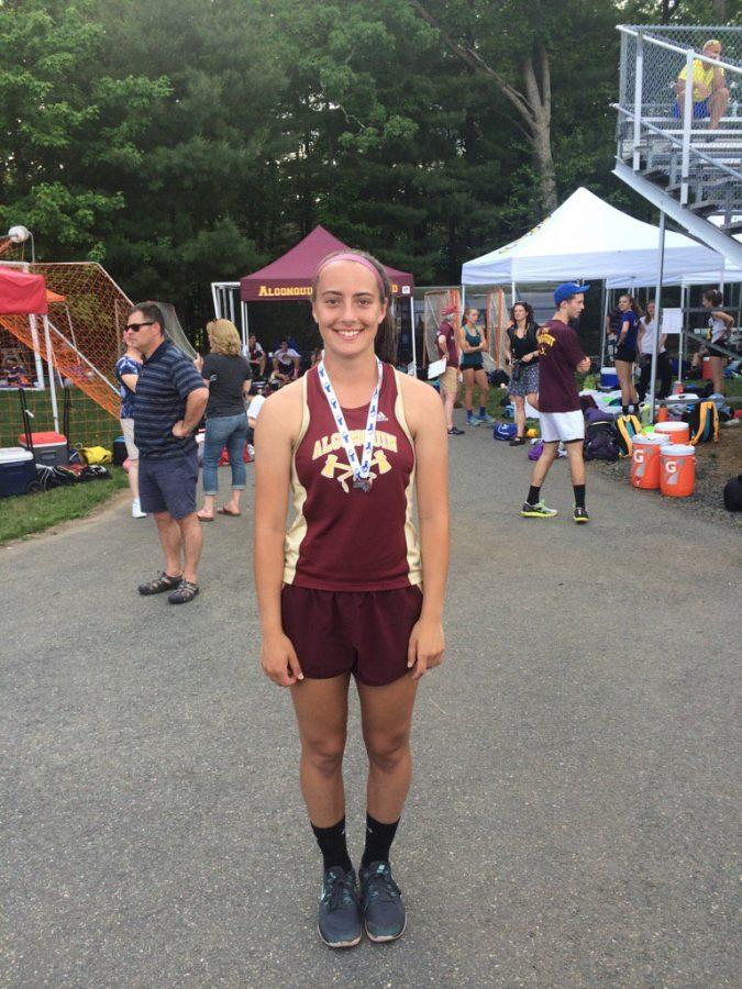 Senior Caroline Leonard poses wearing her medal after placing second in the javelin at the state competition on Saturday, June 4.