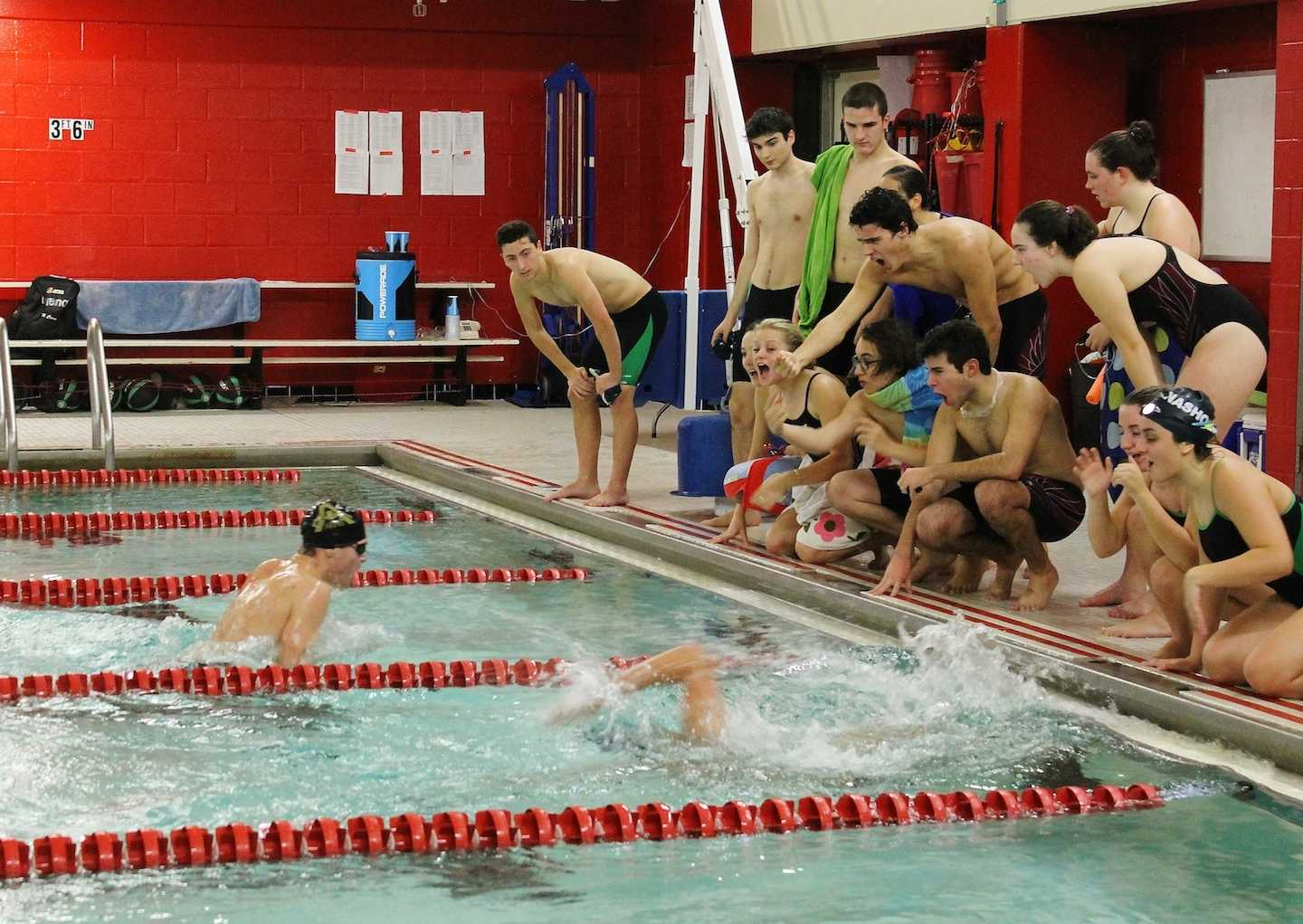 Teammates cheer on sophomore Ray Cerro during the 200 IM event against Nashoba.