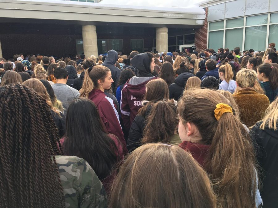 Students fill the sidewalk to head back inside as the walkout comes to a close.