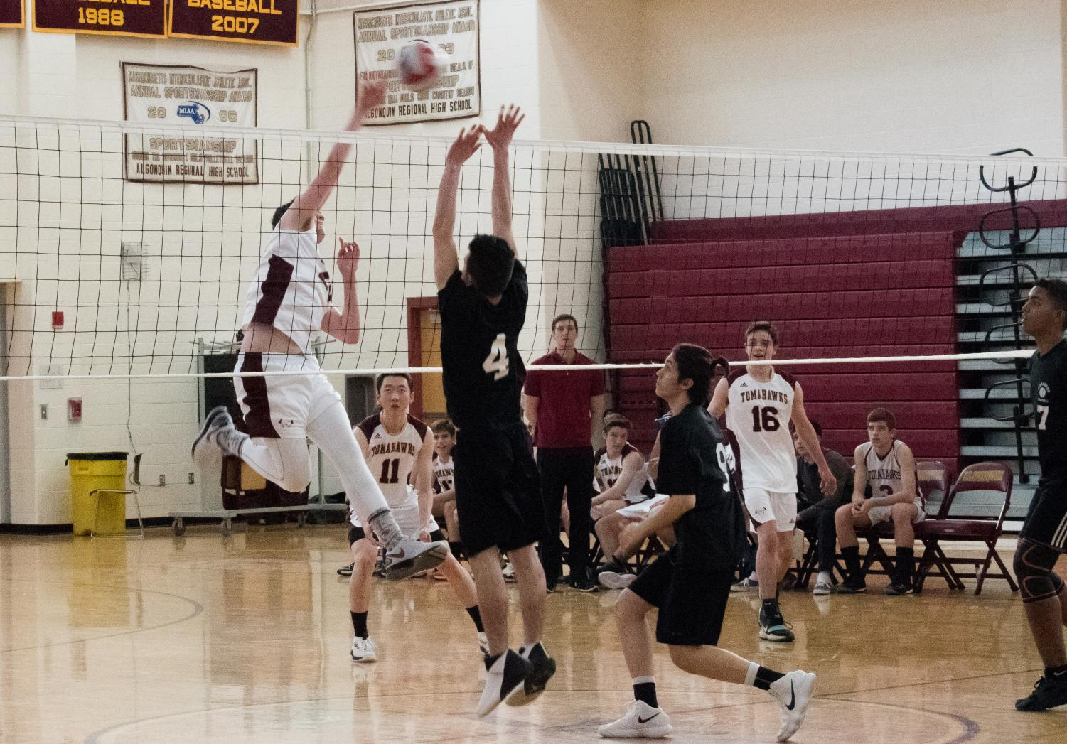 Senior Cam Poutre spikes the volleyball while his opponent jumps up for a block.