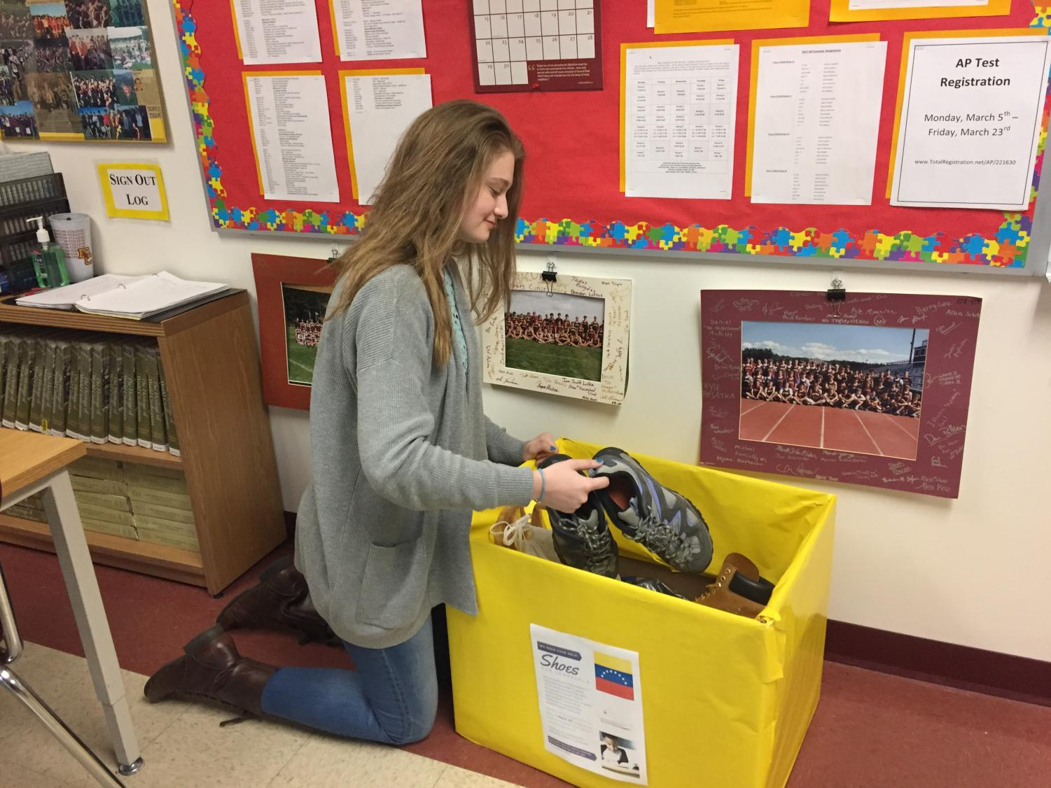 Junior Anna Hoskins placed boxes in classrooms around the school in efforts to collect shoes for children in Venezuela.