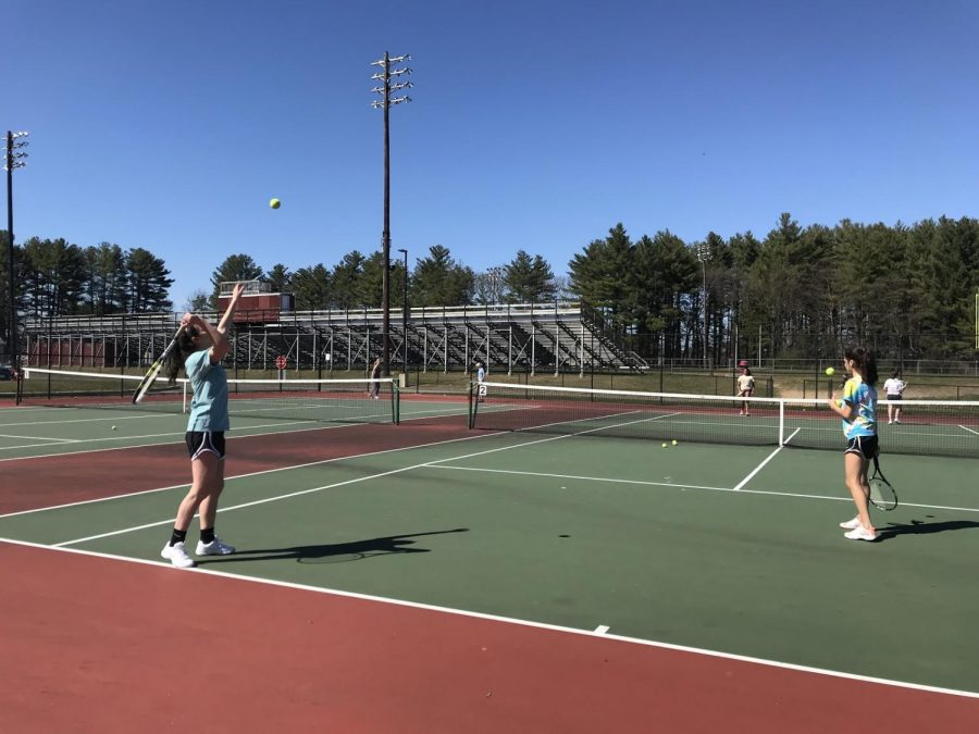 Senior+Leah+Lidsky+serves+a+powerful+ball+over+the+net+with+her+doubles+partner+junior+Mia+Barletta.