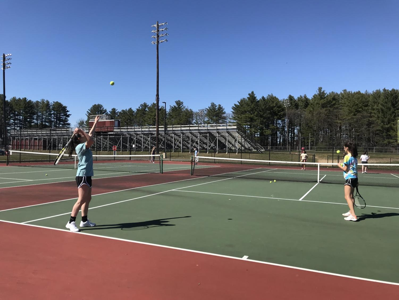 Senior Leah Lidsky serves a powerful ball over the net with her doubles partner junior Mia Barletta.