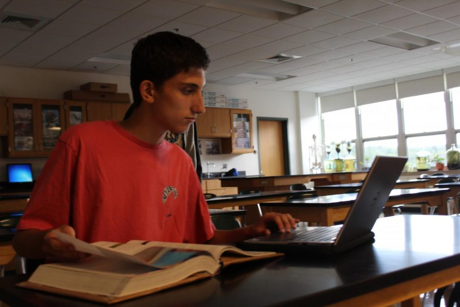 Senior Xander Simon utilizes his laptop in class to do some of his work.