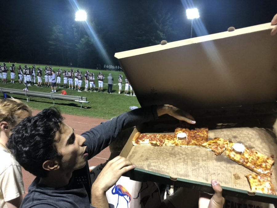 Senior Amir Bagheri takes a slice of pizza for a snack in the middle of the game. He then grabs slices for his friends, almost dropping the box in the process.