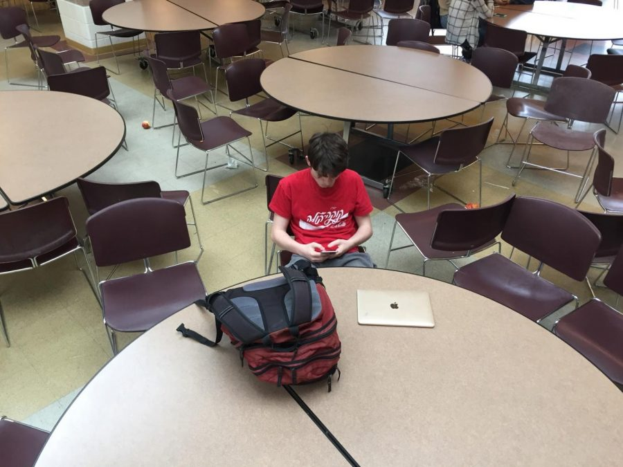 In the cafeteria during seventh period, senior Jack Muirhead browses through his phone.