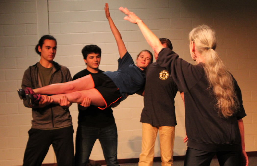 Junior Michael McWilliams, senior Maxwell Petrie and junior Preston Green lift sophomore Miranda Slingluff while choreographer Denise Day instructs during rehersal for