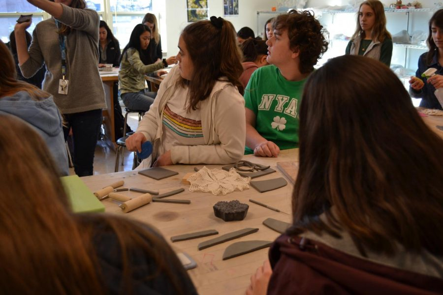 Students listen attentively as art teacher Danielle DeCiero gives directions on how to DIY clay soap dishes in the workshop she offered along with science teacher Catherine Burchat.