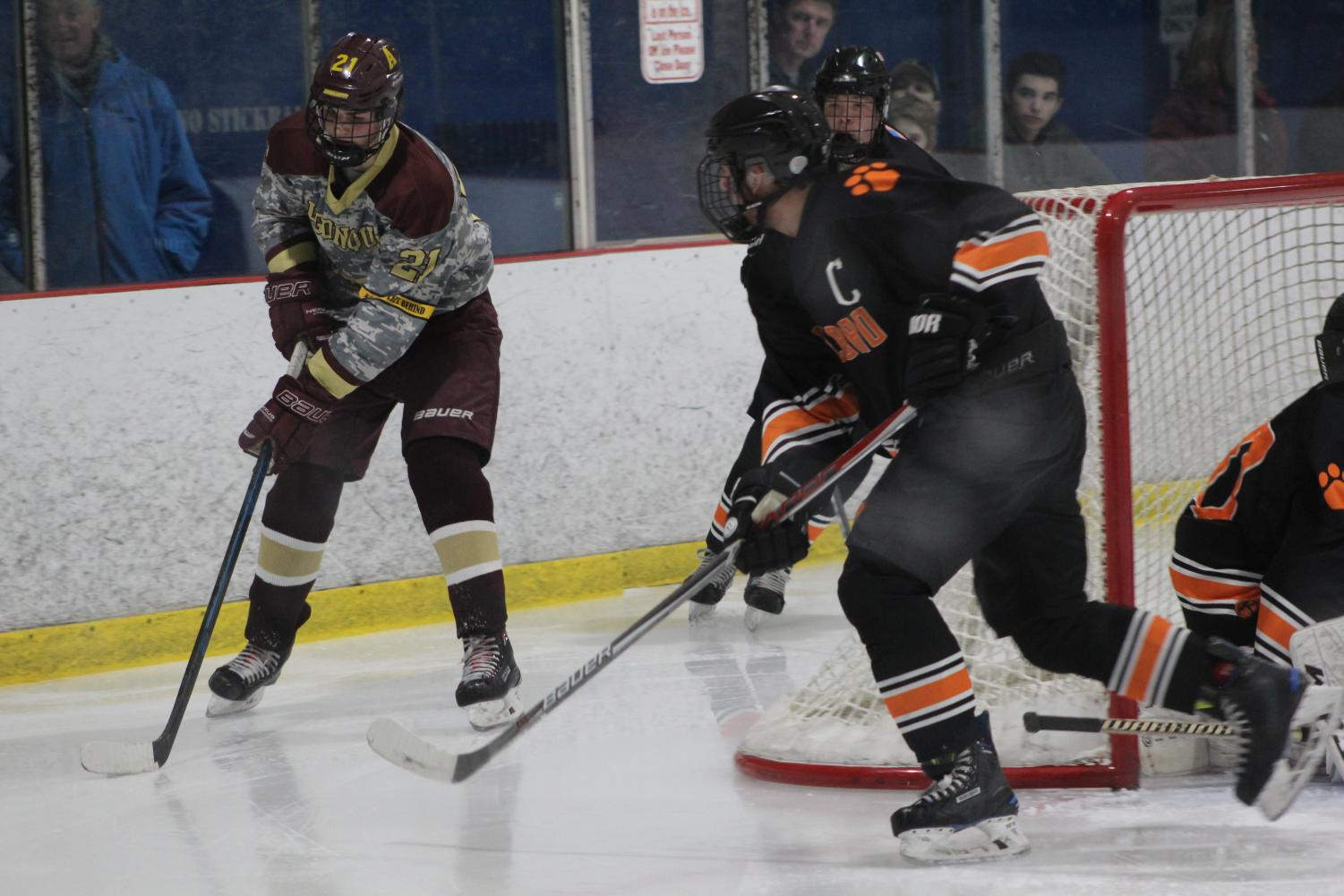 Junior Henry Alford gains control of the puck, as Marlborough plays defense.