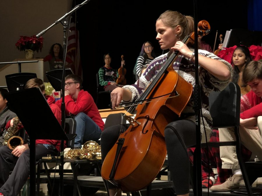 Senior Veronika Jaster plays the cello while the chorus sings a song.