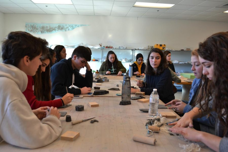 Members of the pottery STEP use carving tools to create their own designs on clay pieces that will soon become soap dishes.