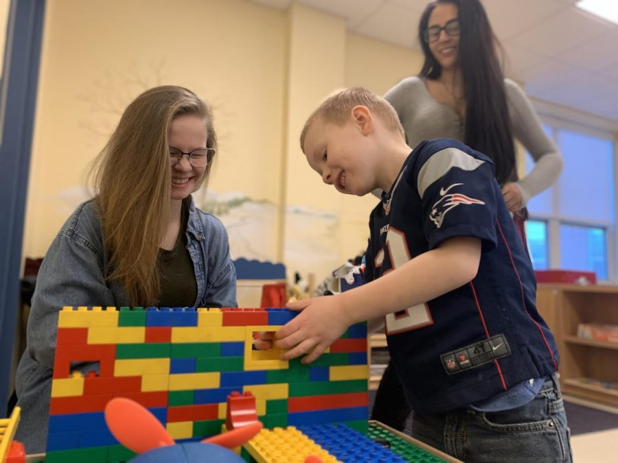 """Junior AbbyGaile Kieler [back right] and senior Elizabeth Rice are two of the high school students who takes the childhood development class. """"Its crazy; throughout my time here I watch them grow up and play with each other and really come out of their shells,"""" Kieler said. Tiny Tomahawk James makes some finishing touches on his lego house with the help of his student teachers."""