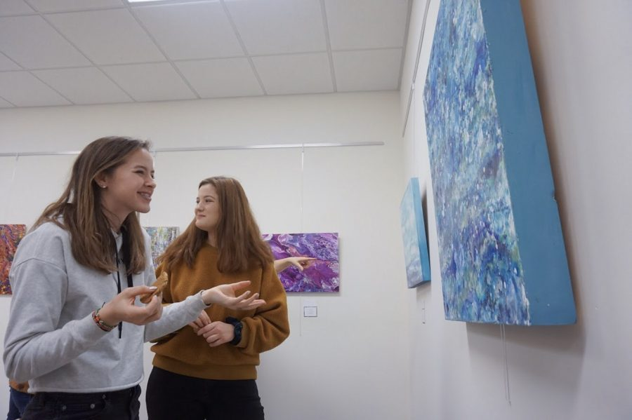Seniors Emily Philbrook [left] and Meredith Eppen [right] admire one of Hayden's ocean- inspired paintings as they enjoy complimentary desserts and refreshments.