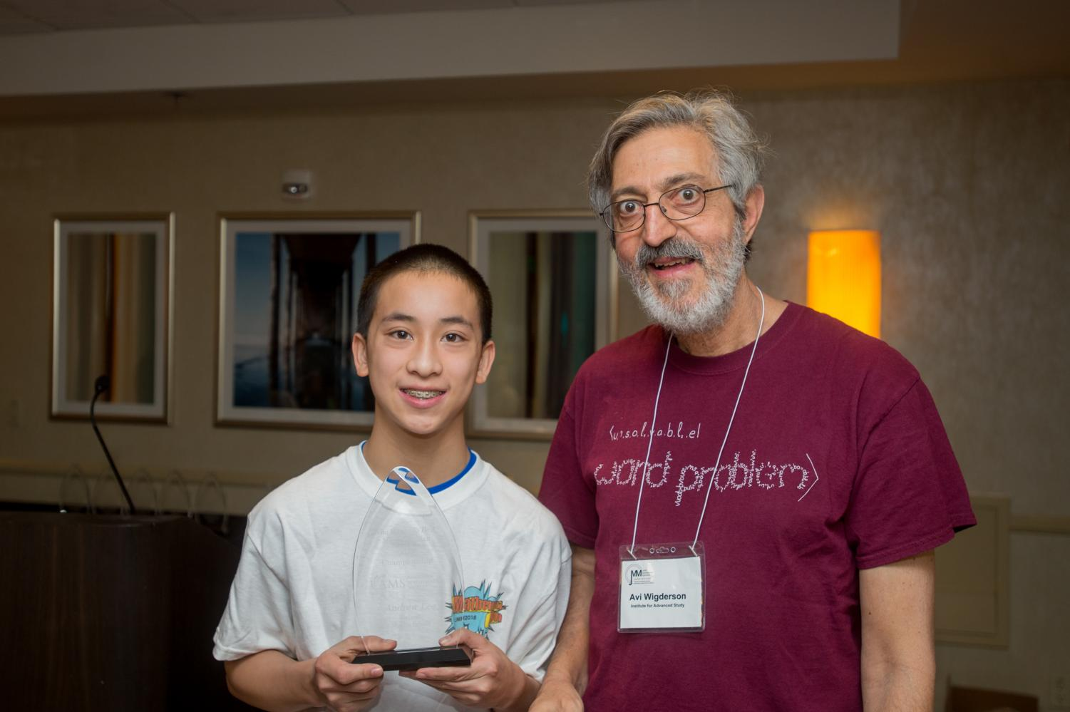 Andrew Lee holds his award proudly with Avi Wigderson from the Institute for Advanced Study at the 2018 Who Wants to be a Mathematician awards breakfast.