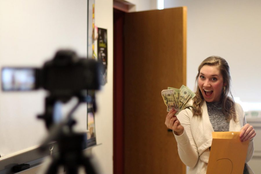 Senior Annalise Loizeaux poses with cash to promote the game show.