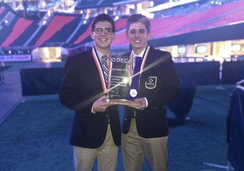 Seniors Josh Harmon and Sam Forbush hold their second place trophy at the Mercedes Benz stadium at ICDC last year.