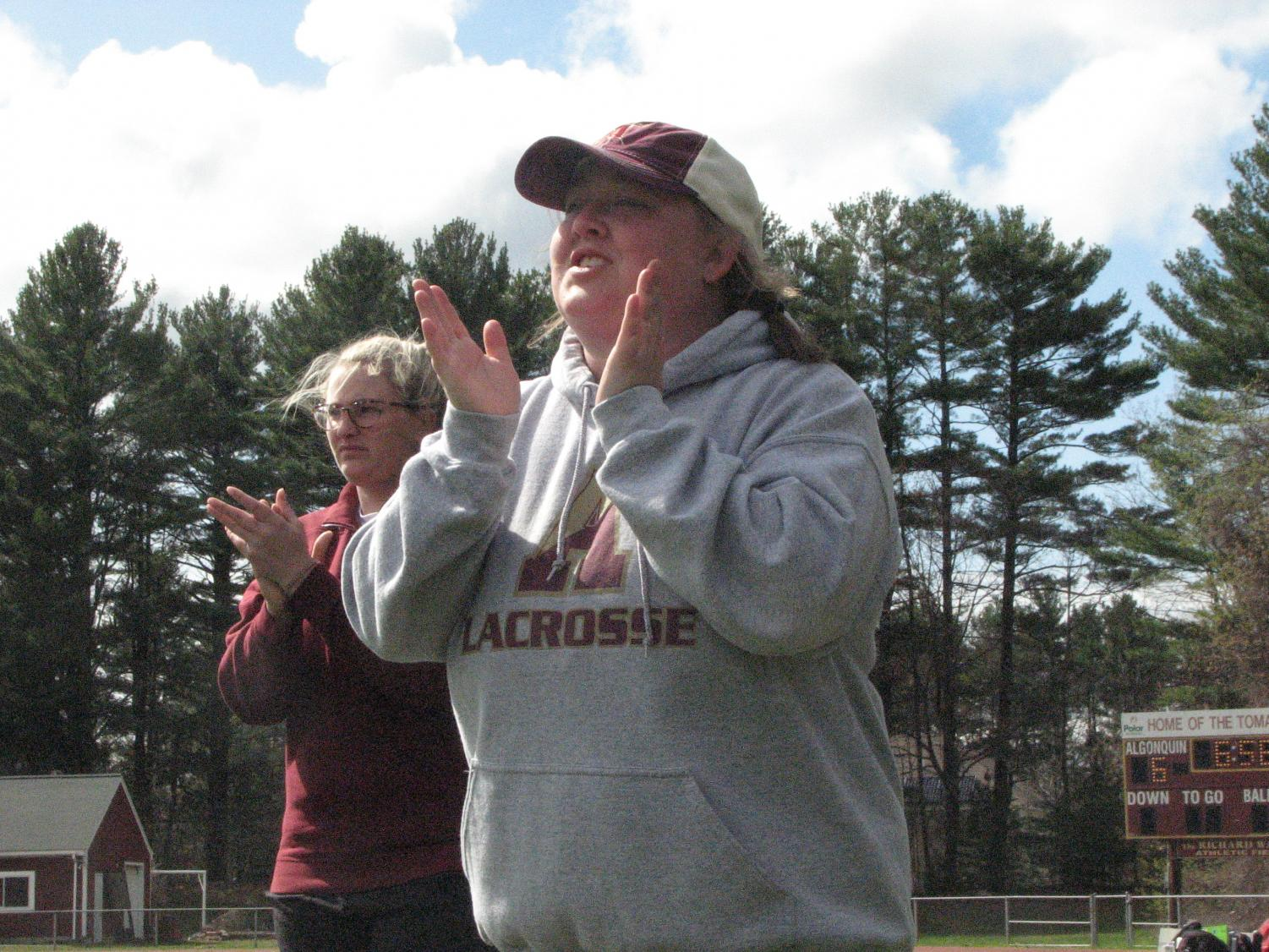 Class of 2013 graduate Emma Decker and new girls' lacrosse coach cheers on the team after they score a goal on Dover-Sherborn on April 27.