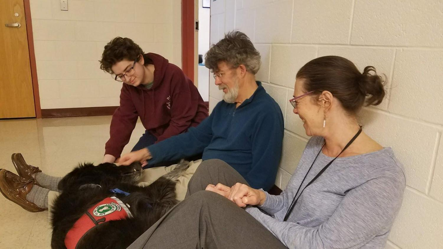 Senior Carlyn Schwingbeck, Ed Harrow of Pets and People, and special education teacher Beth Mintz play with Tucker the therapy dog. Mintz and Scwingbeck have worked with the Pets and People organization to bring therapy dogs into Algonquin to provide relief for students.