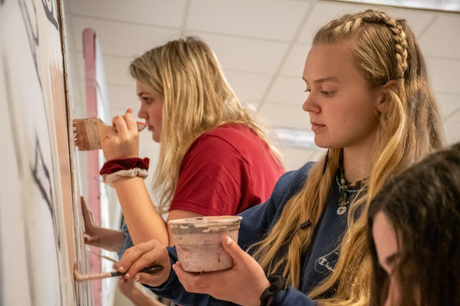 As the spring art show approaches, freshman Colleen Mulligan and sophomore Lauren Decker focus intently to finish their art work.