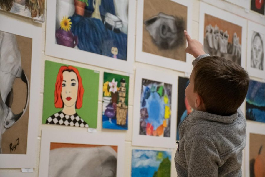 A young boy points at a painting on display which has caught his attention.