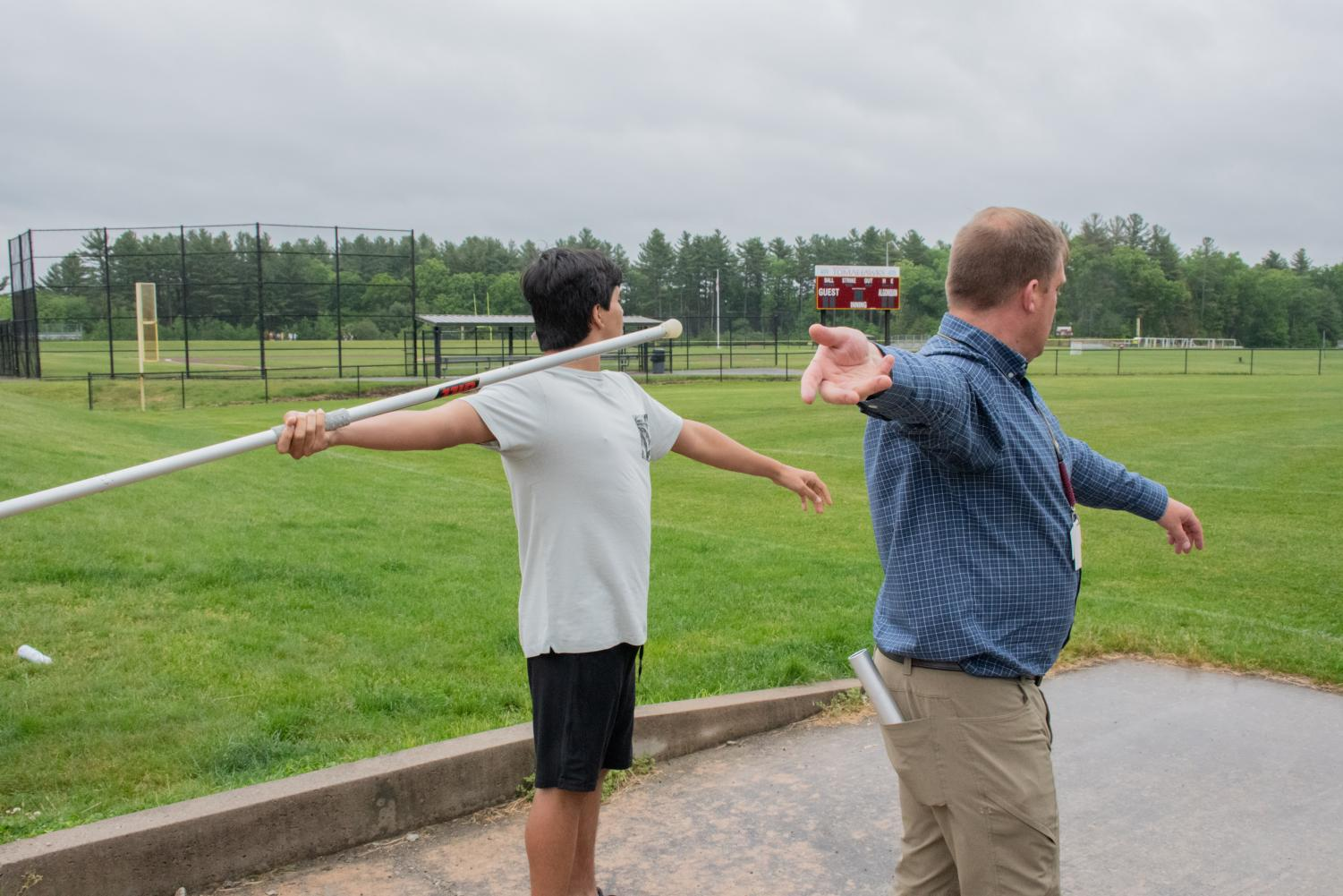 Unified track coach Kevin Hausmann shows a unified track member how to correctly throw the javelin.