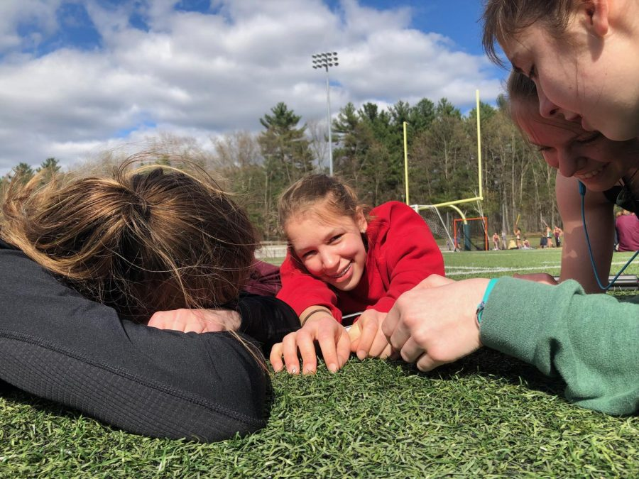 """Every track meet, junior Karmyn Shreeve relaxes with friends before the races begin. """"I'm running the two mile later but we're just jamming out to Bohemian Rhapsody right now,"""" Shreeve said."""