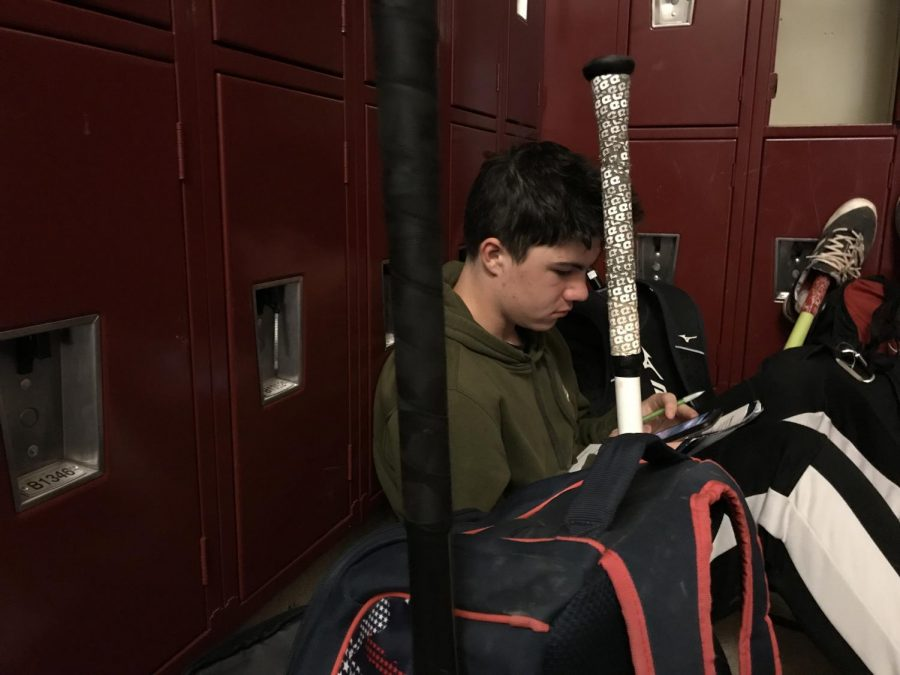 """After school, freshman Andrew Carlson does his homework in the locker room before a baseball game. """"I have to find a way to fit in school work and sports,"""" Carlson said. """"This is a good time to do it because it is quiet and I don't have much time when I get home."""""""