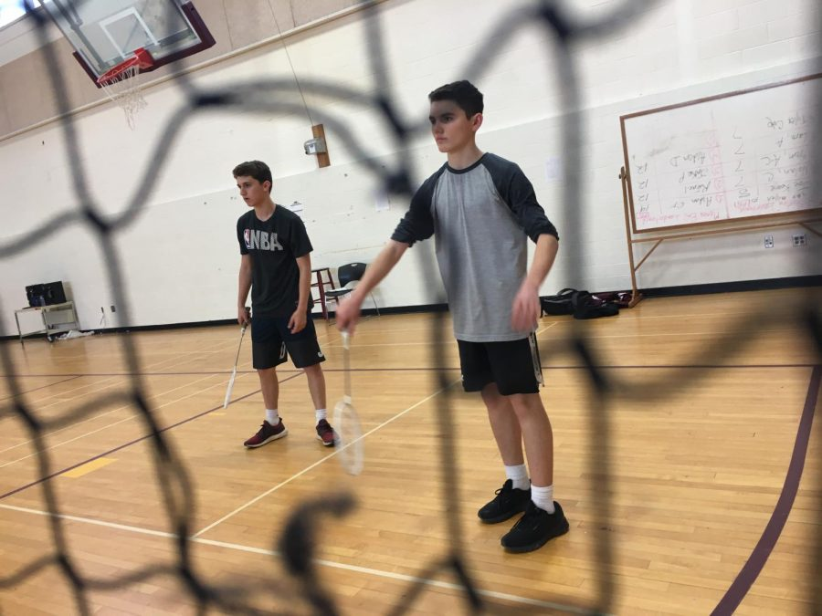 In a friendly game of badminton, freshmen Jeremy Strauss and Aidan Dilo prepare themselves for a serve from the other team in the C gym during third period gym class.