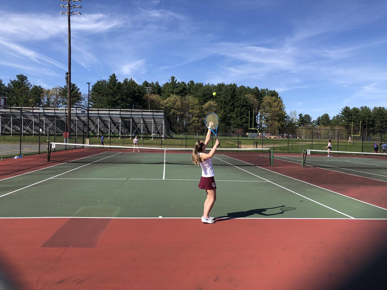 Freshman Olivia Almy delivers a dynamic serve against Marlborough opponent Marissa Petty in the first singles tennis match on May 6.