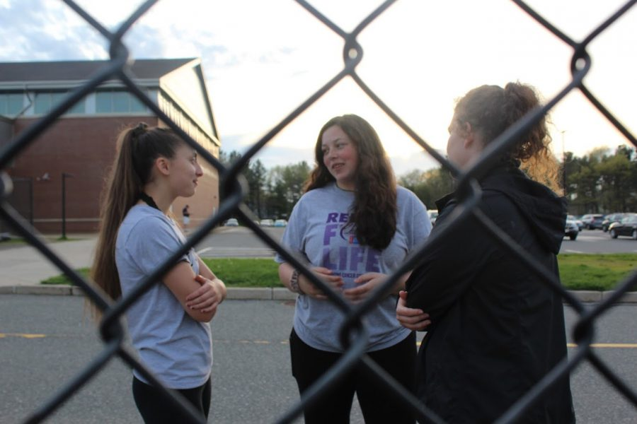 Sophomores Jamie Smith, Marin Klein and junior Kate Feeney have a conversation together as they watch the volleyball tournament unfold.