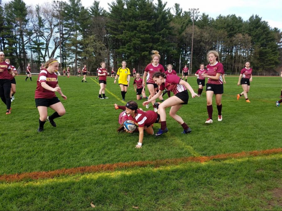 Senior Lydia Grist (ground, center) tackles Weymouth player. Junior Kailey Carlton (right center), junior Olivia Lamy (center, back) and sophomore Victoria Witkowski (right) are quick to assist.