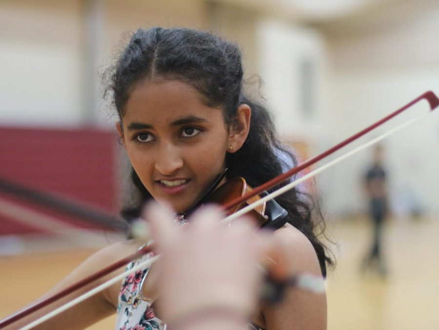 "Freshman Srishti Kaushik tuned her violin and warmed up by briefly reviewing her pieces. ""It's our last concert!"" Kaushik said, ""And we're going to make it amazing."""