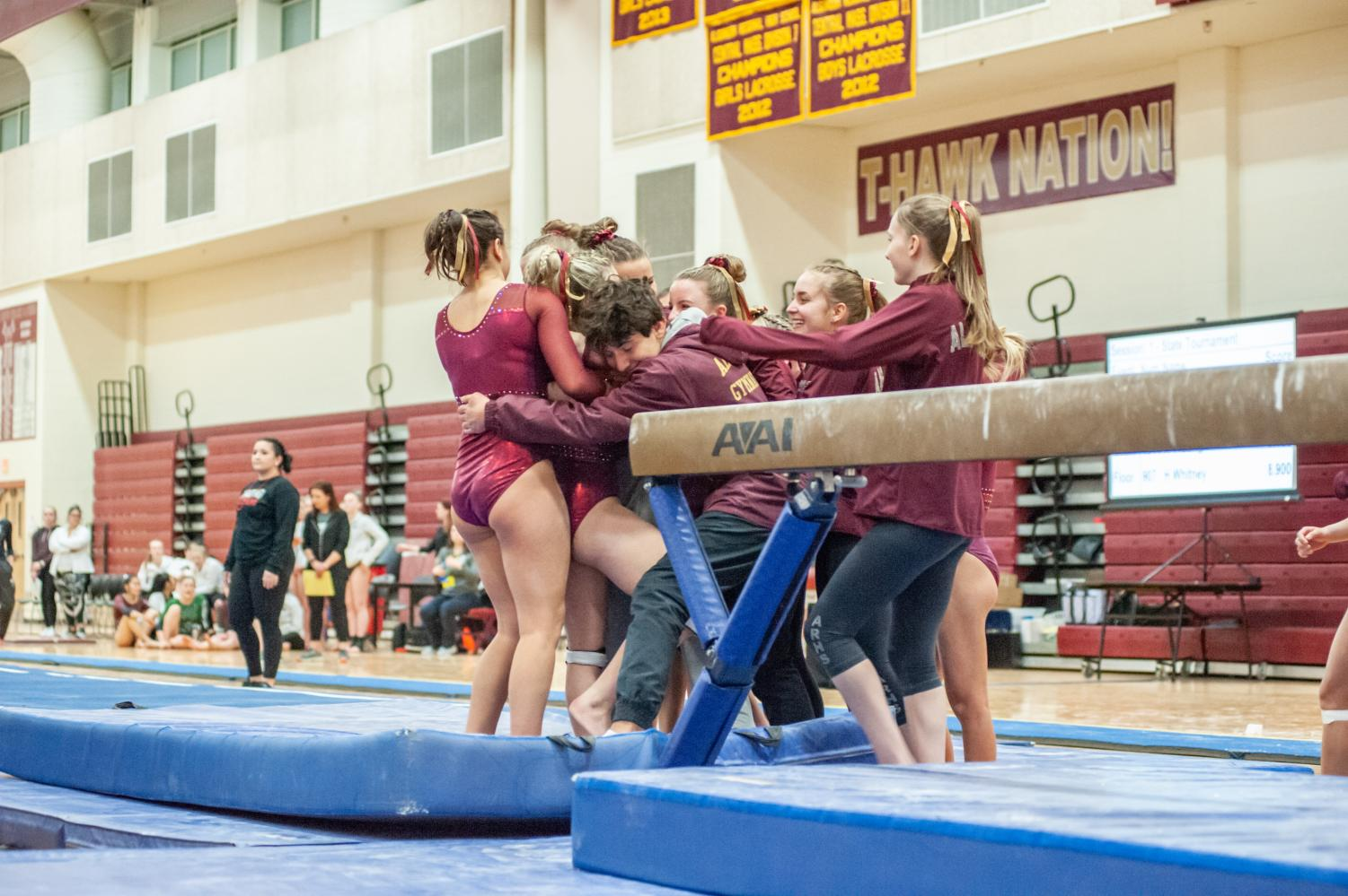 The gymnastics team celebrates at the State Championship on March 2 where they placed sixth.