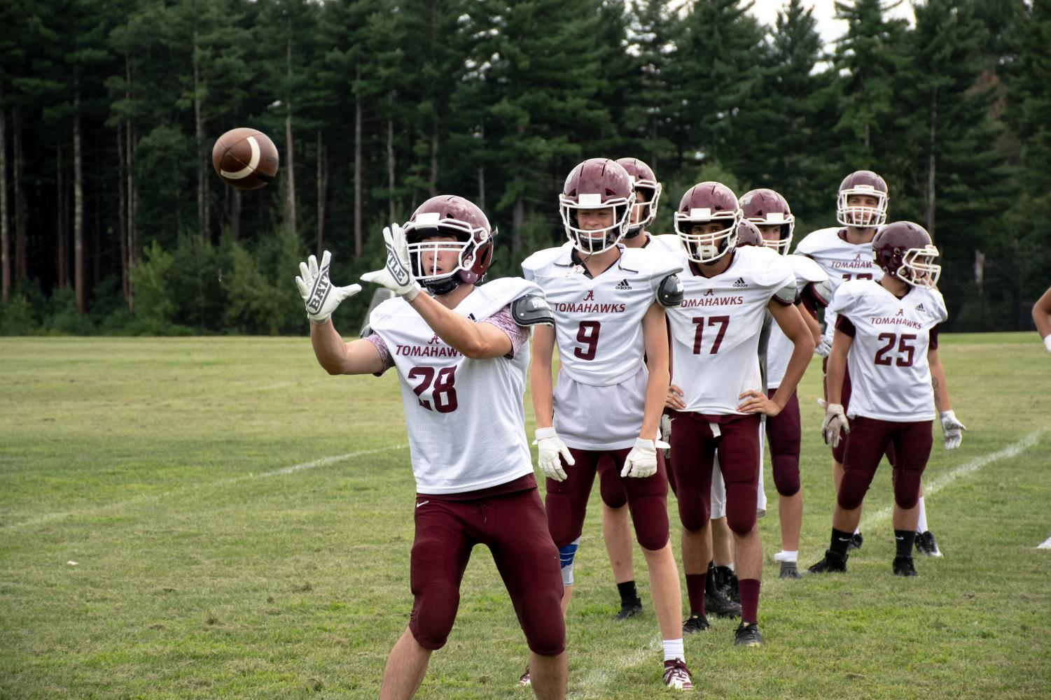 During+a+receiver+drill%2C+senior+Yanni+Batsolakis+attempts+to+catch+the+ball+thrown+to+him+as+his+teammates+look+on.