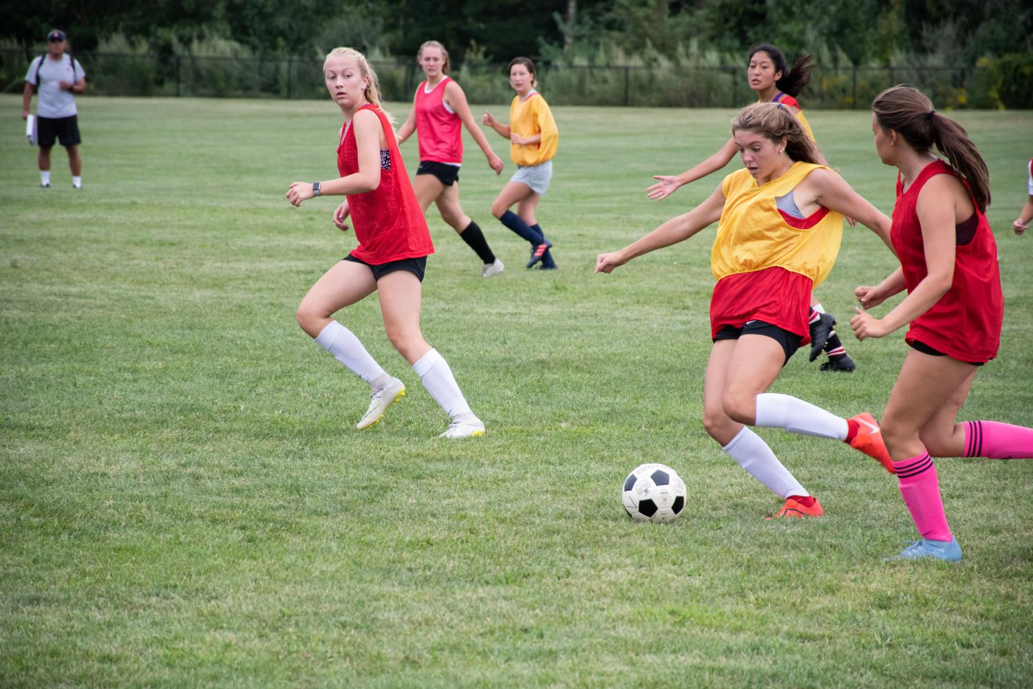 Freshman+Sadie+Candela+looks+to+advance+the+ball+through+defenders+on+both+sides+to+pass+to+her+teammates+upfield.+Candela+ended+up+making+the+varsity+team.