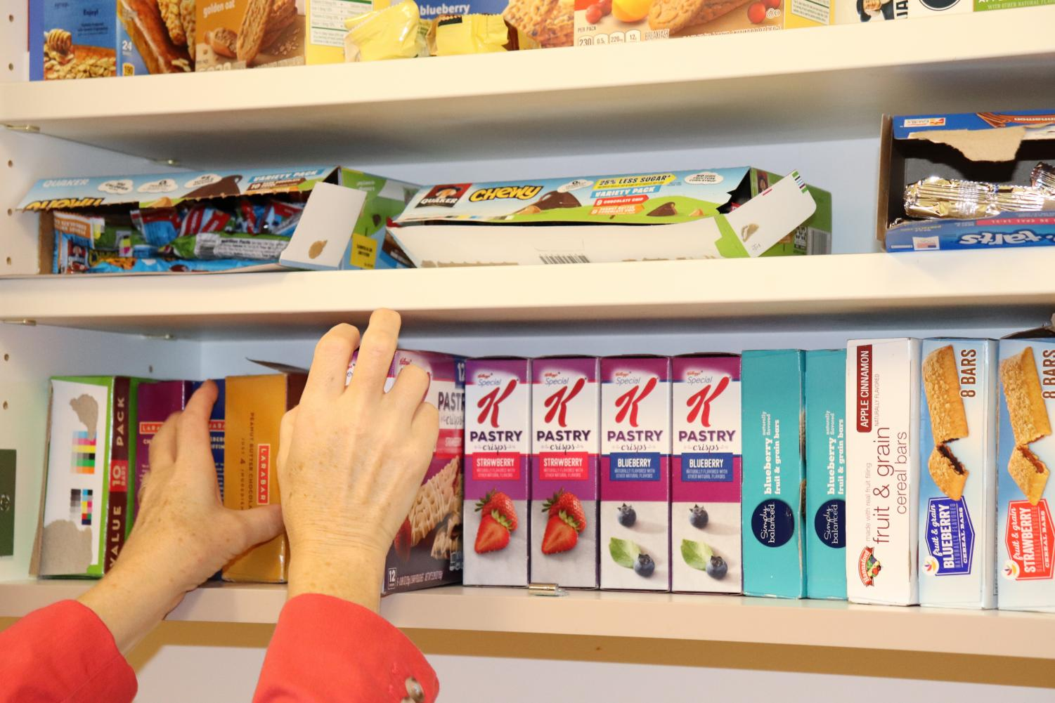 Science teacher Aimee Selby adjusts breakfast bars in one of the fully stocked cabinets of the new Algonquin Breakfast Club. Students that can't eat a nourishing breakfast at home are able to go in and sign out food in the morning before school.